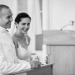 bride and groom share a laugh at the altar