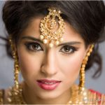 Indian wedding bride in red sari and gold tikka with pearls - MUA Glam by Jeet
